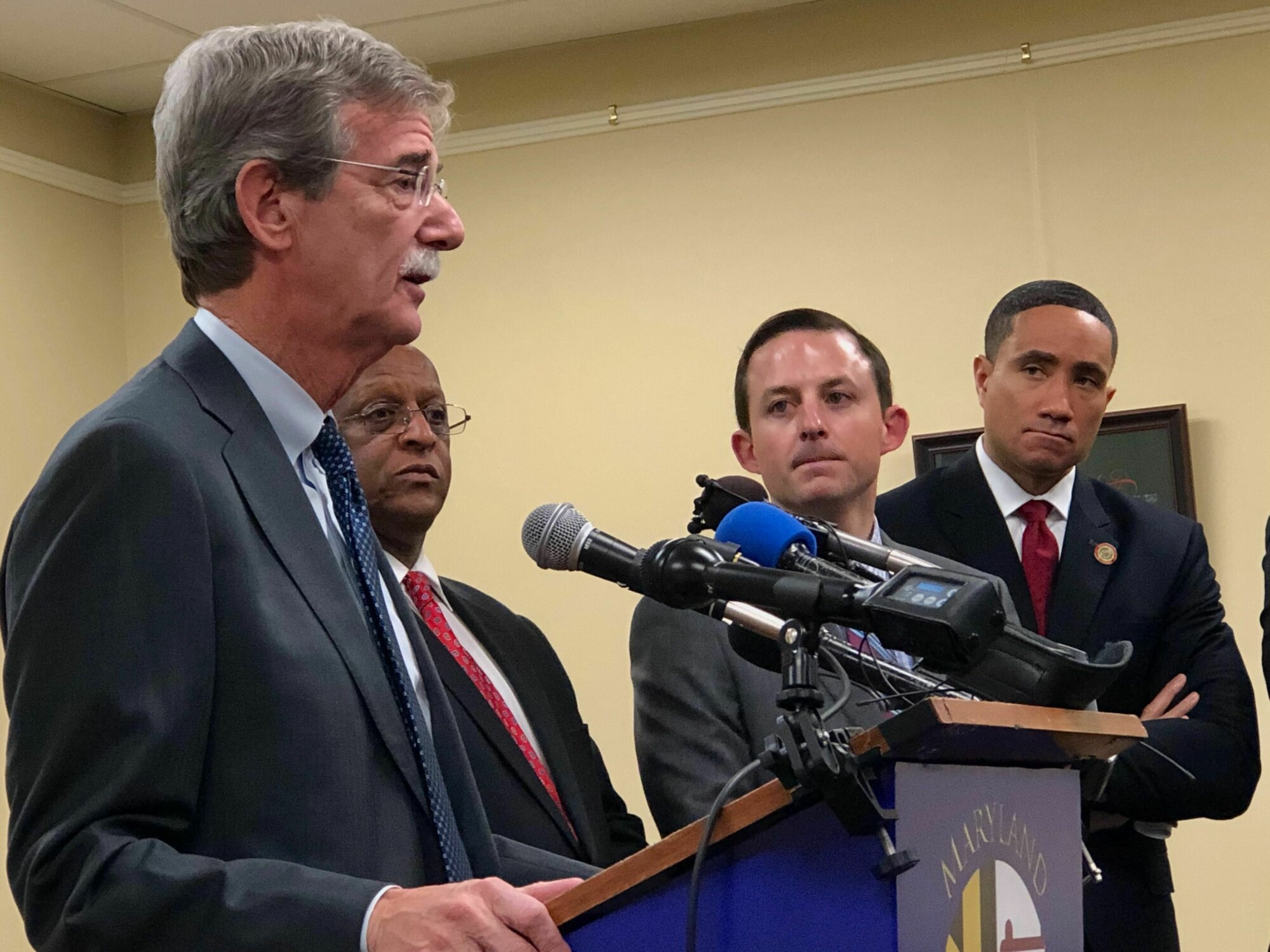 Maryland Attorney General Brian Frosh, Baltimore Mayor Jack Young, Senate President Bill Ferguson and Sen. Will Smith speak in support of ending the practice of suspending driver's licenses. (WTOP/Kate Ryan)