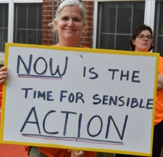 "A gun violence prevention activist holds a sign with the powerful message, ""now is the time for sensible action."" ERPOs, also known as &ldquoRed Flag Laws,"" are a common-sense solution."