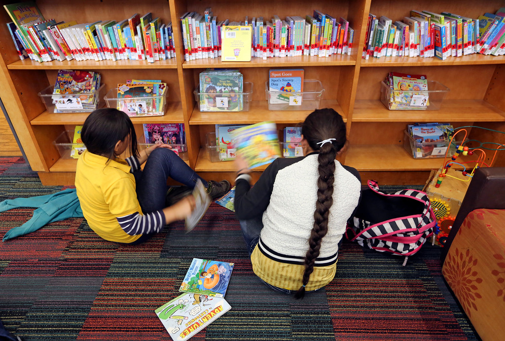 Two children sitting in front of bookshelf at library