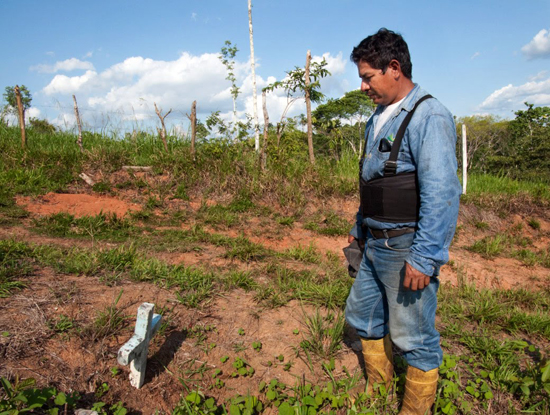 Antonio Jaime Yanan Gomez, 42, stands at the grave site of his daughter.