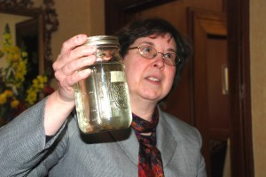 Bev May holds a jar of contaminated water