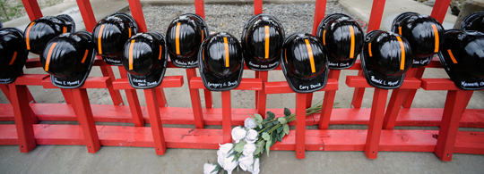 Mine helmets and painted crosses sit at the entrance to Massey Energy's Upper Big Branch coal mine Tuesday, April 5, 2011, one year after 29 miners were killed there.