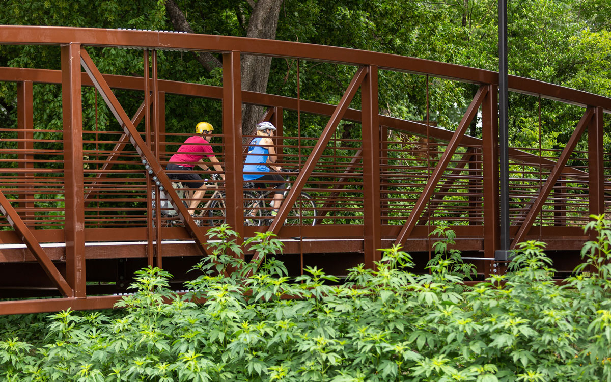 Two people biking on bridge over Boggy Creek