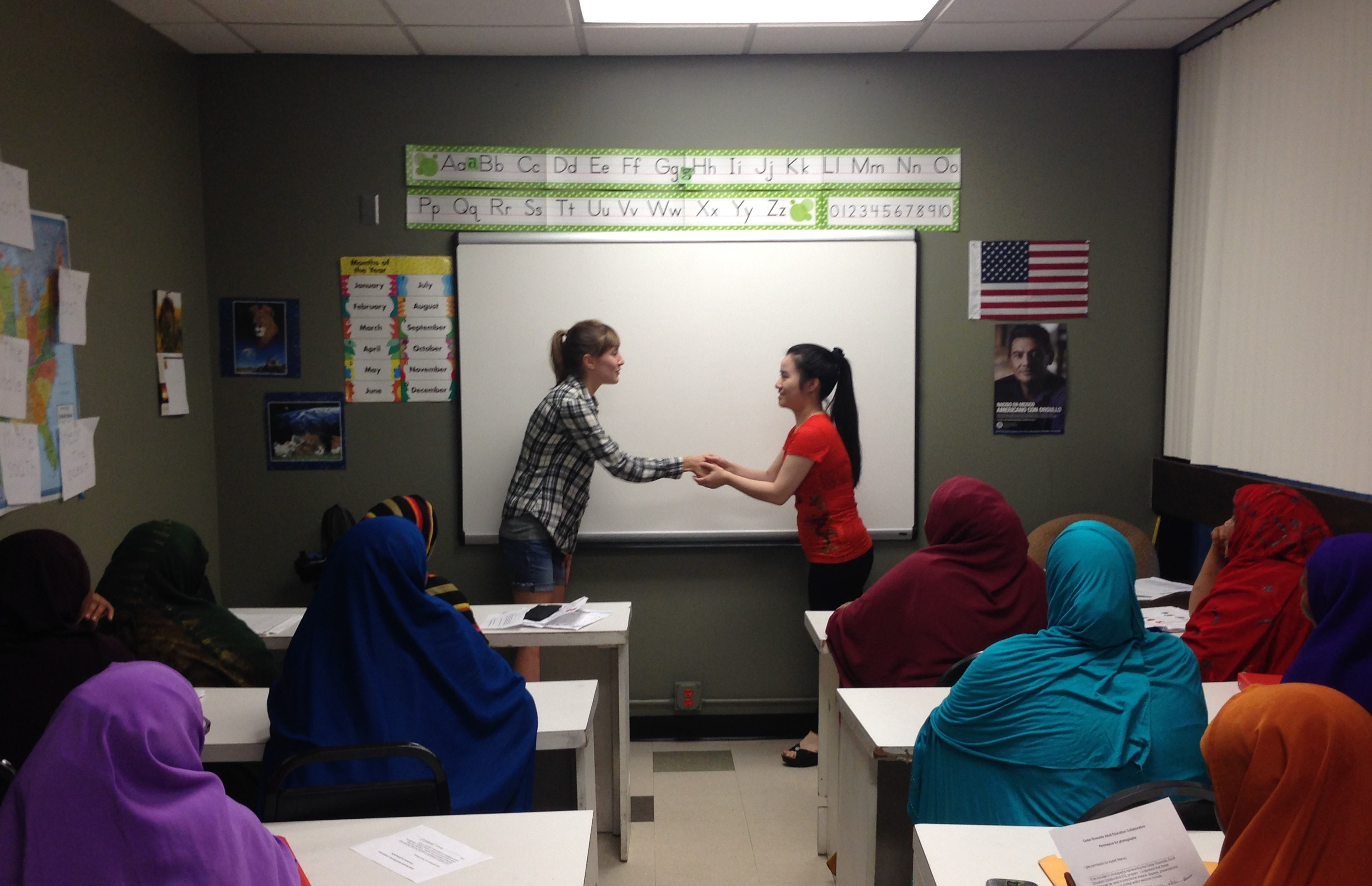 Volunteer shaking hands with a teacher at the front of the room