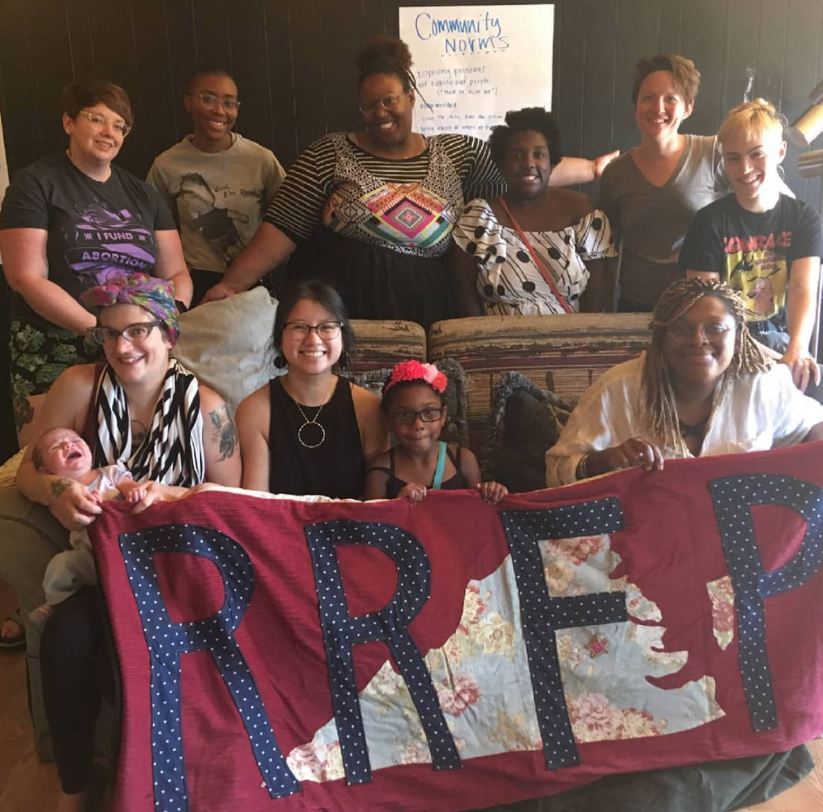 group photo of rrfp volunteers and collective members behind the RRFP quilted banner