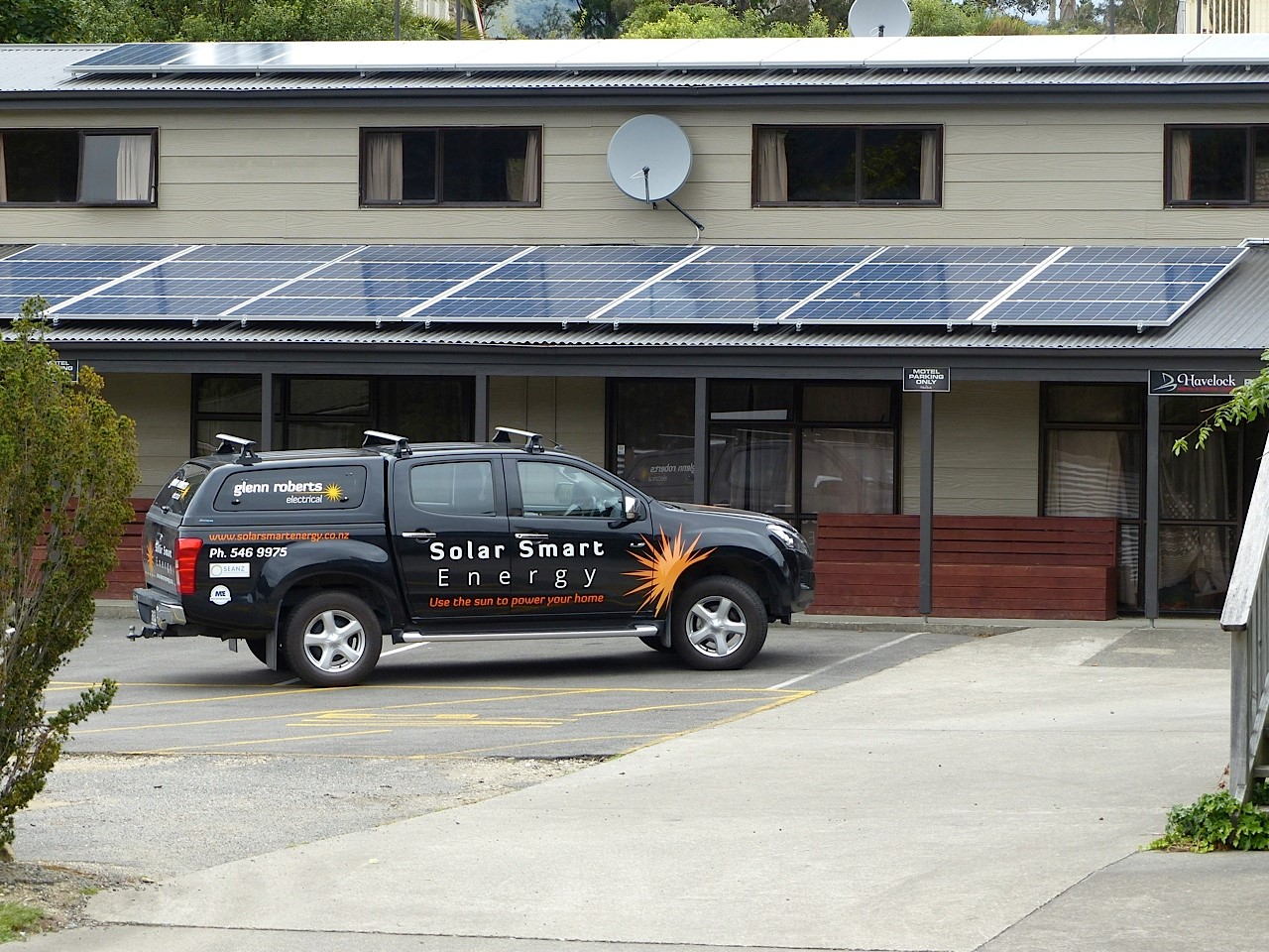 Solar Smart Energy vehicle parked in front of motel with solar panels visible on the roof.