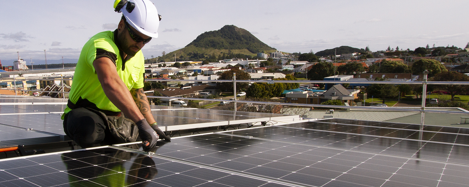 worker installs solar panels on roof of building with Mt Maunganui in the background