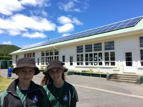 two Avalon Intermediate school students stand in front of a classroom with new solar panels on the roof