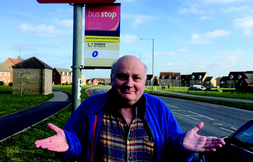 Simon Harries at busstop looking for buses