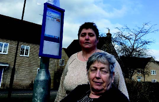 Sue Austin and Christine Whelan at a bus stop looking for missing buses