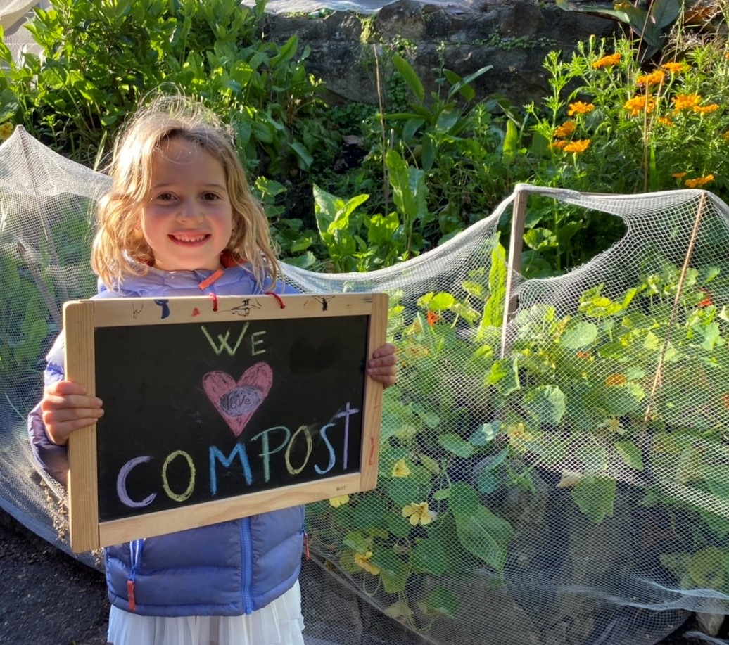 Girl holding compost sign