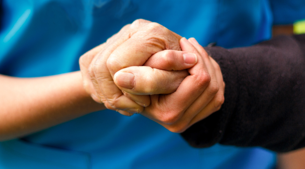 Caregiver and client holding hands