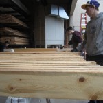 Students in the Construction Tech class at Sitka High are applying a preservative treatment to the future deck of the bike shelter to protect the wood.