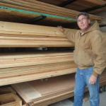 Mr Randy Hughey stands by boards of Sitka Spruce, which will be used as apart of the bike shelter's roof.