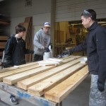 Teamwork makes applying the wood preservative on the shelter's future deck go by quickly.