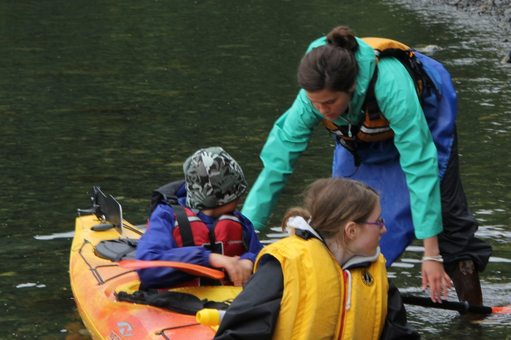 Mary Wood helps 4-H members get settled into their kayak before going on the water or the first time.