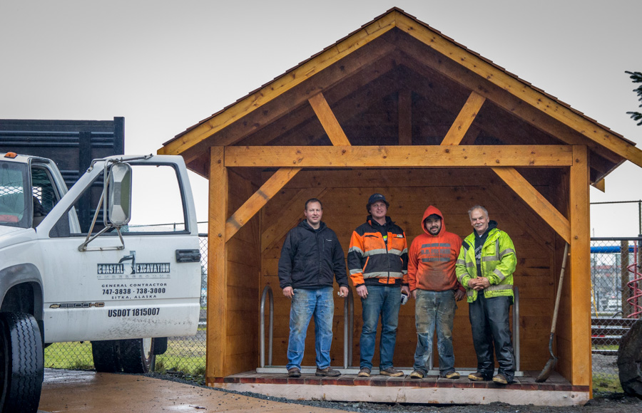 Chris Pearson and his crew from Coastal Excavation pose in the shelter after transporting it to its final home.