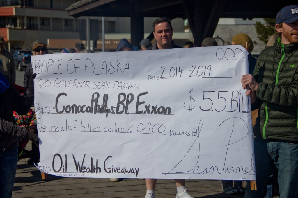 Sitkans hold a fake check made out to ConocoPhillips, BP, and Exxon at an SB 21 Rally on April 4, 2014.