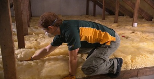 Man installing insulation in roof cavity.