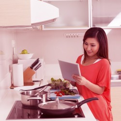 woman reading recipe on tablet while coking