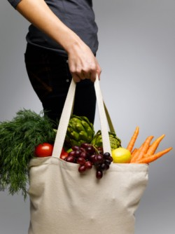 potassium-rich fruits and veggies in a shopping bag
