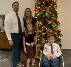 Zachary S and his mother, father, and sibling pose in front of a Christmas tree