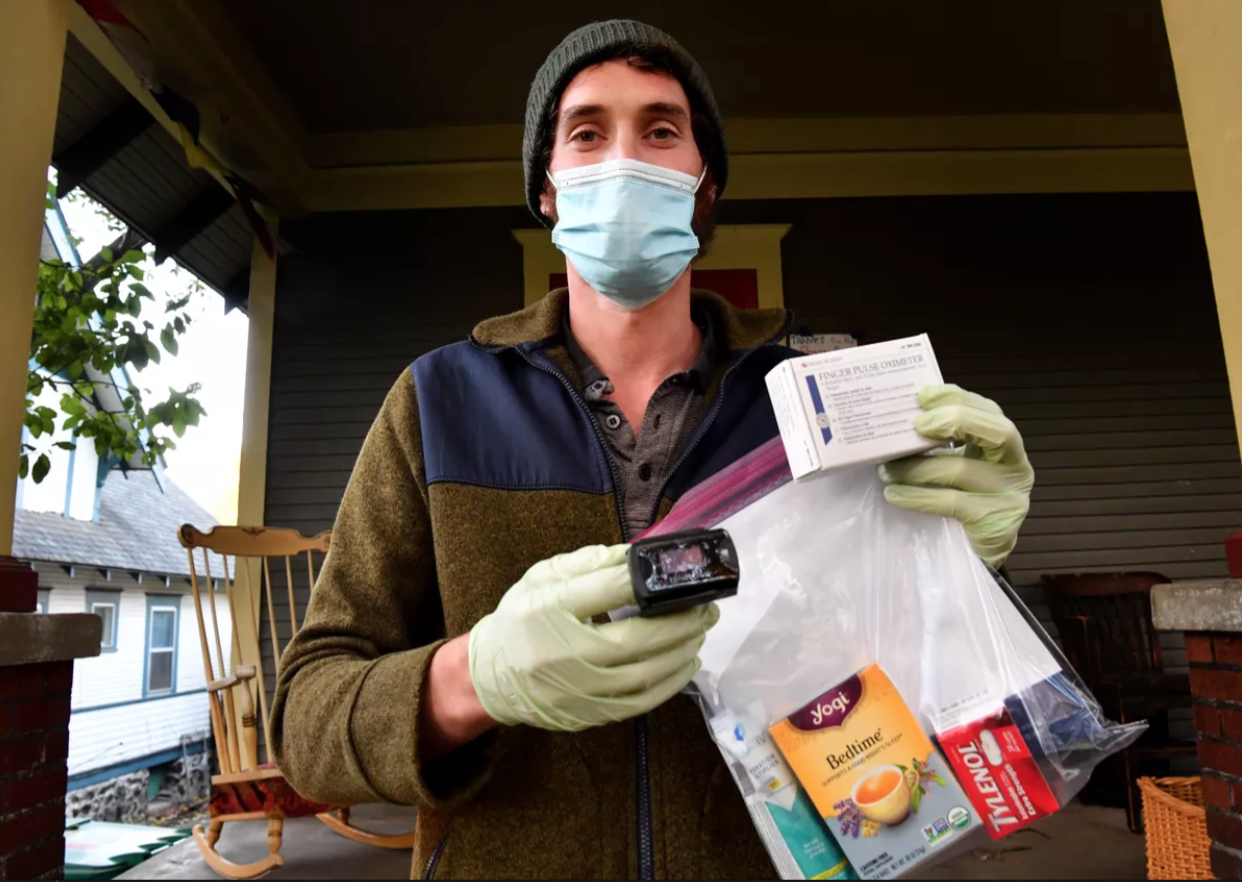Jeremy Taylor, a volunteer with the Community Health Monitoring Program, holds a pulse oximeter and a care package of supplies the organization delivers to people who test positive for COVID-19. (Tyler Tjomsland/THE SPOKESMAN-REVIEW)