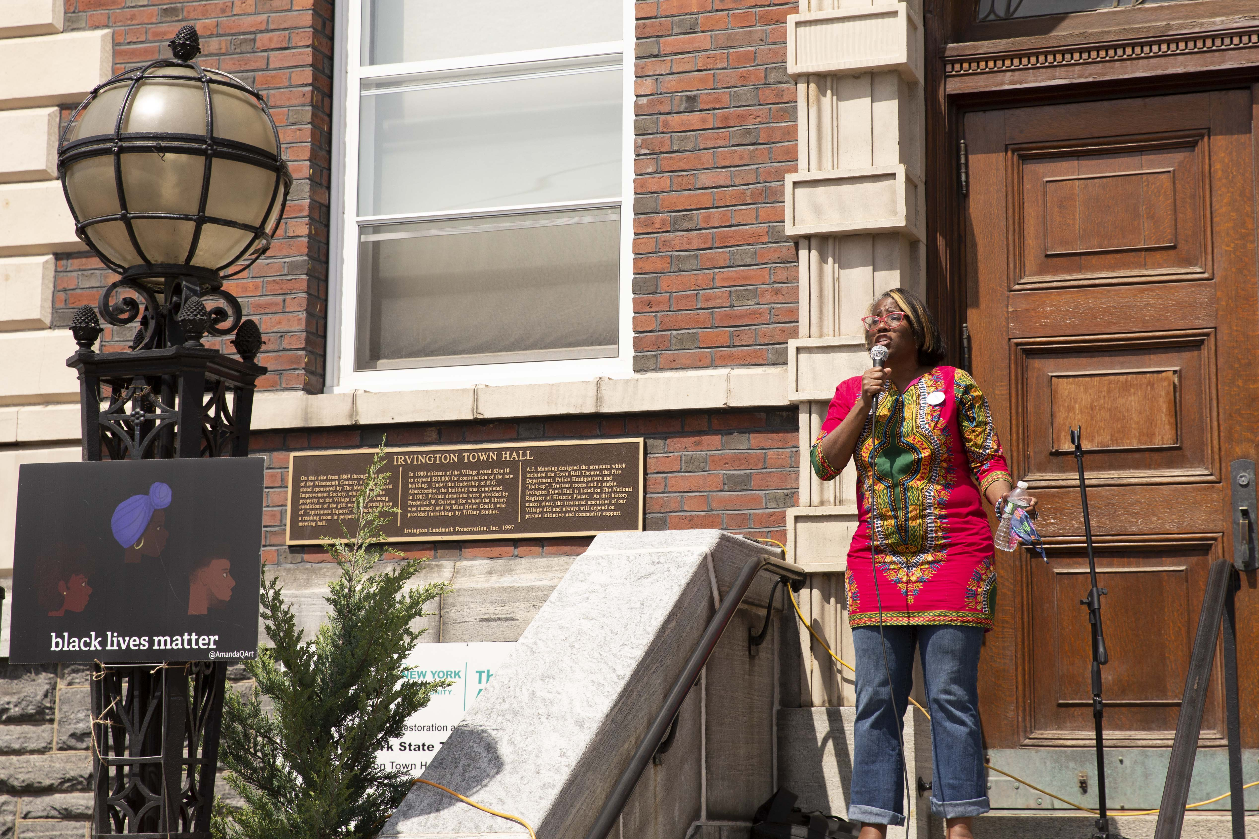 Tasha speaking in front of Irvington Town Hall with BLM sign
