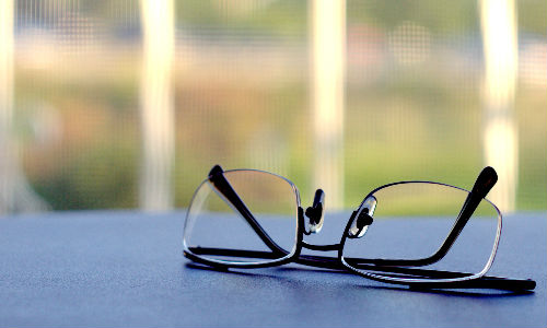 A pair of glasses resting on a blue surface