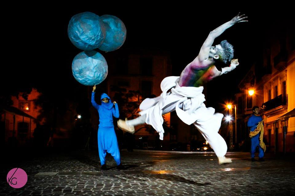 A performer dressed in blue with three large balloons and a performer dressed in white jumping on a city street at night