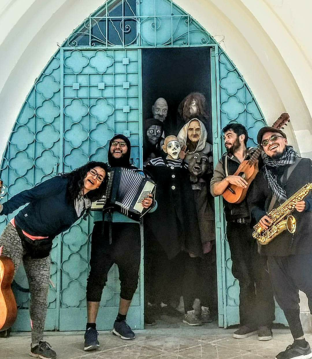 Members of La Quinta Teatro holding musical instruments stand in front of an arched doorway with people in masks standing in the doorway