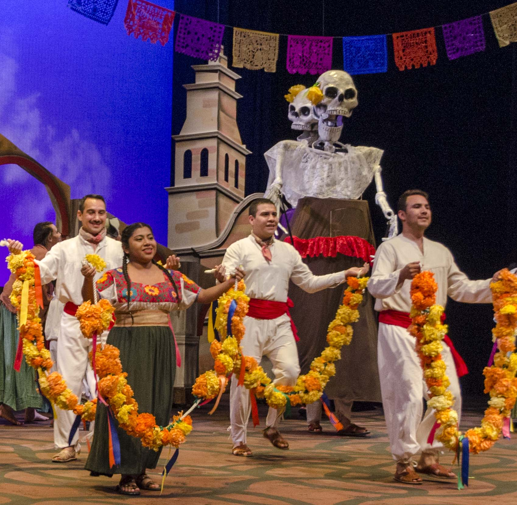 Scene from Macario - dancers holding chains of paper flowers dance in front of large skeleton puppets