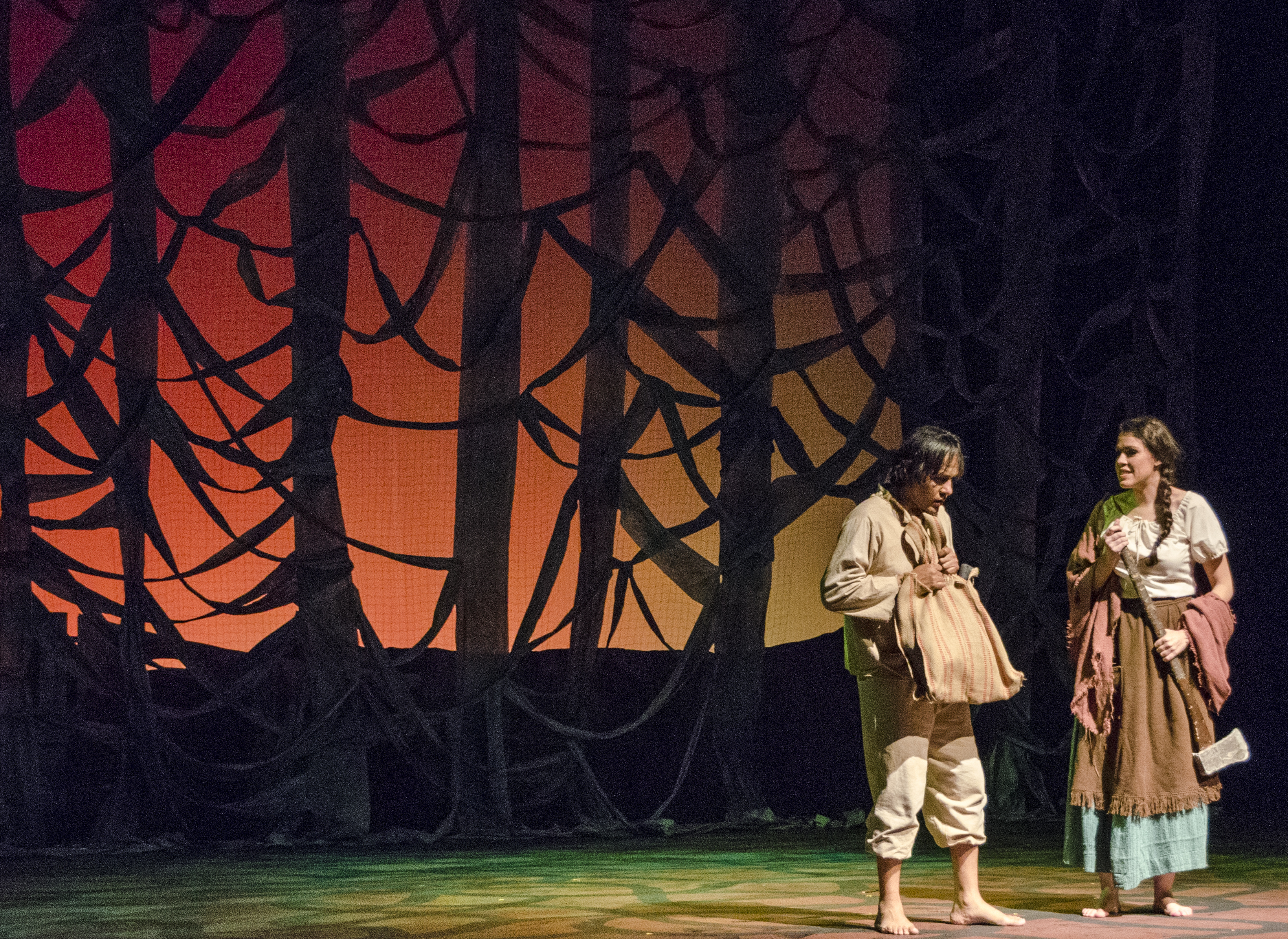 Scene from Macario - Macario and his wife stand in front of a fabric forest drop