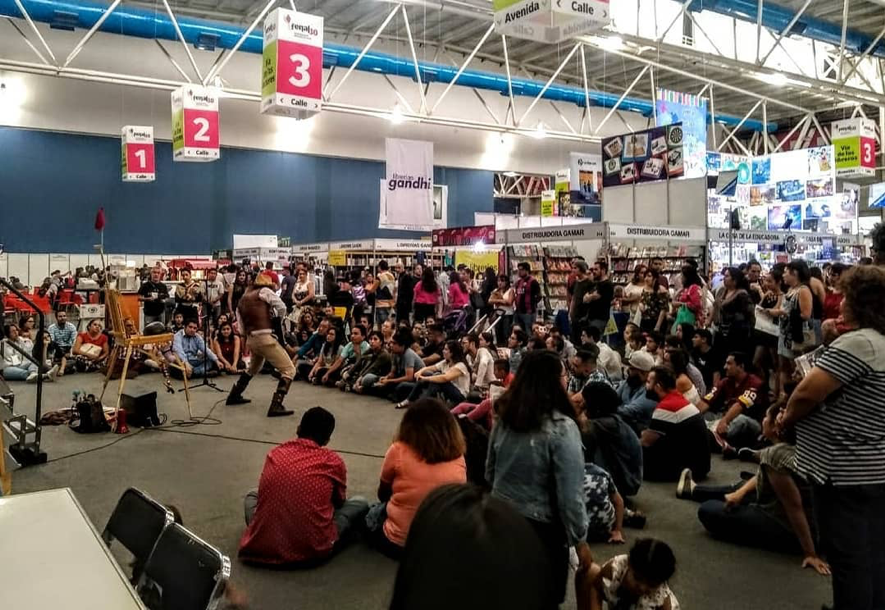 A performer standing in the middle of a crowded semi-circle audience members in a large exhibition hall