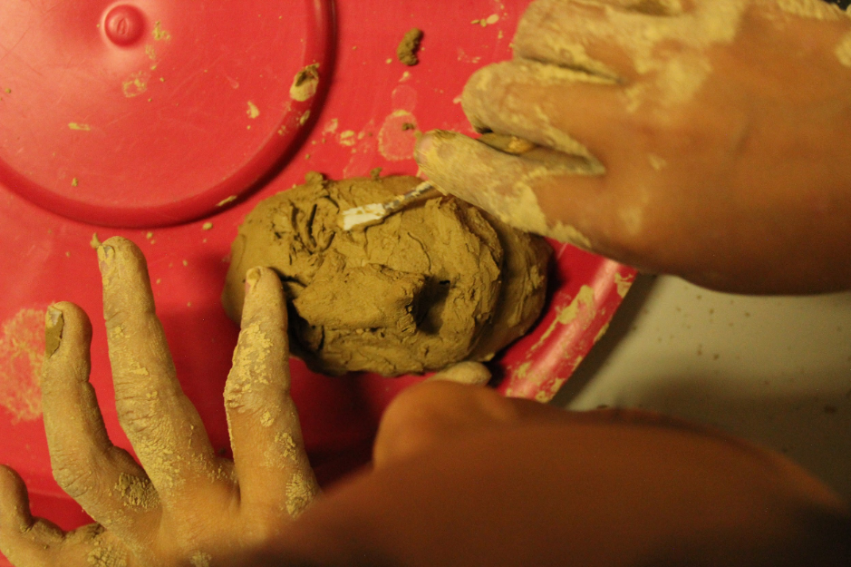 Close up of hands sculpting a small face out of clay