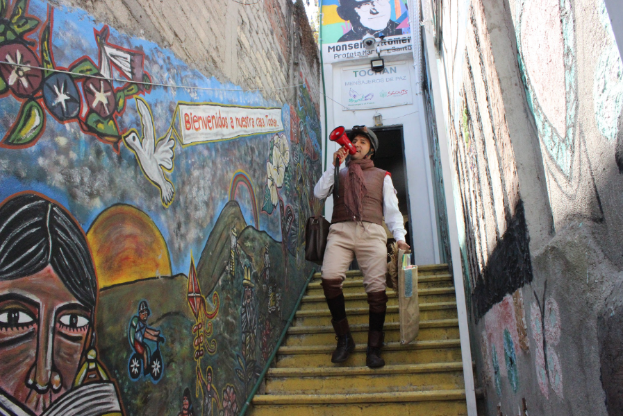 A performer descends a staircase next to a large colorful mural while holding a megaphone