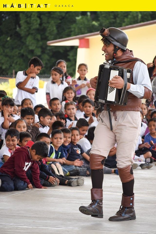 A performer with an accordion in front of an audience of young children