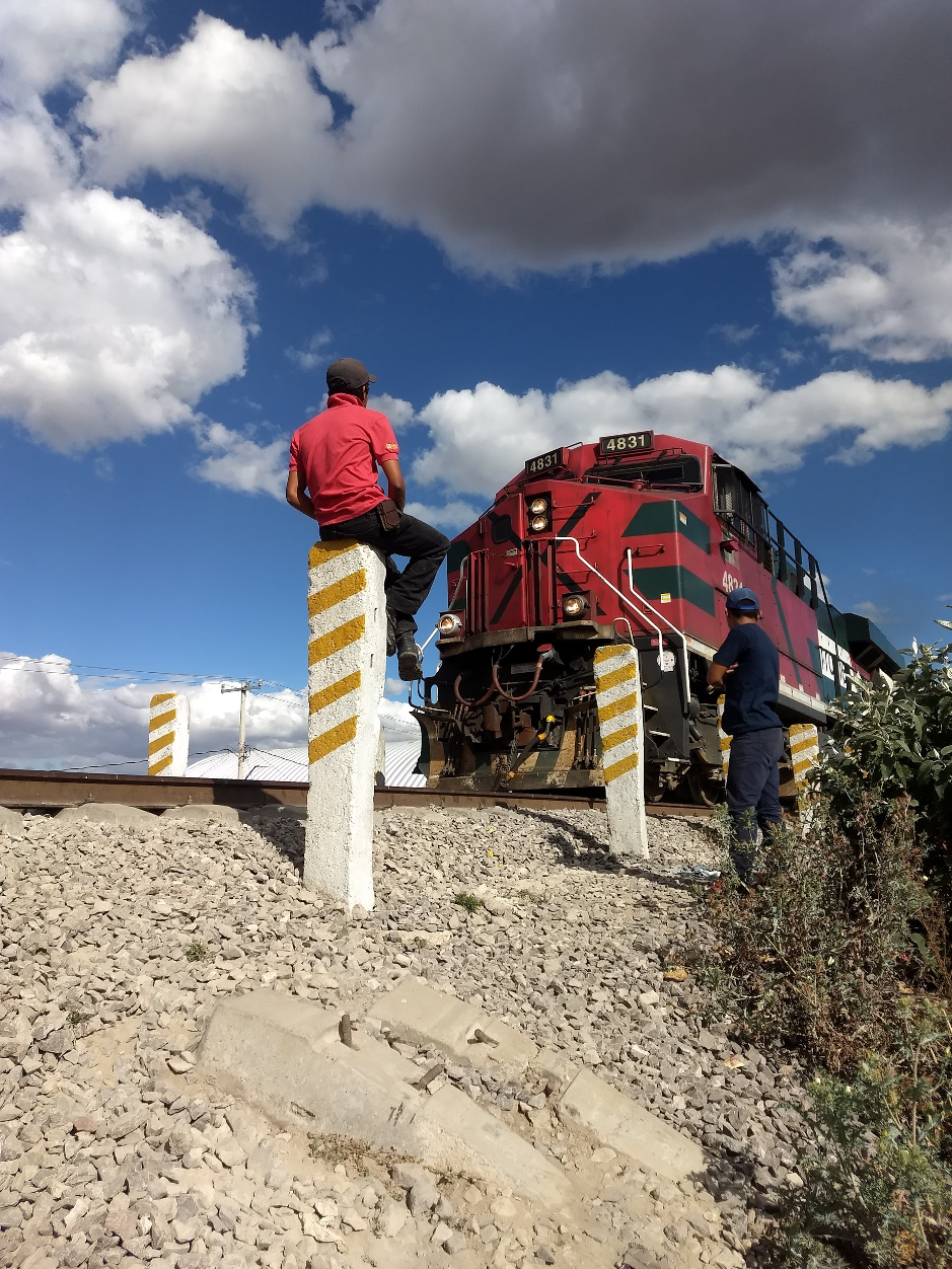 A man sits on a post and another man stands next to train tracks with a large red train engine