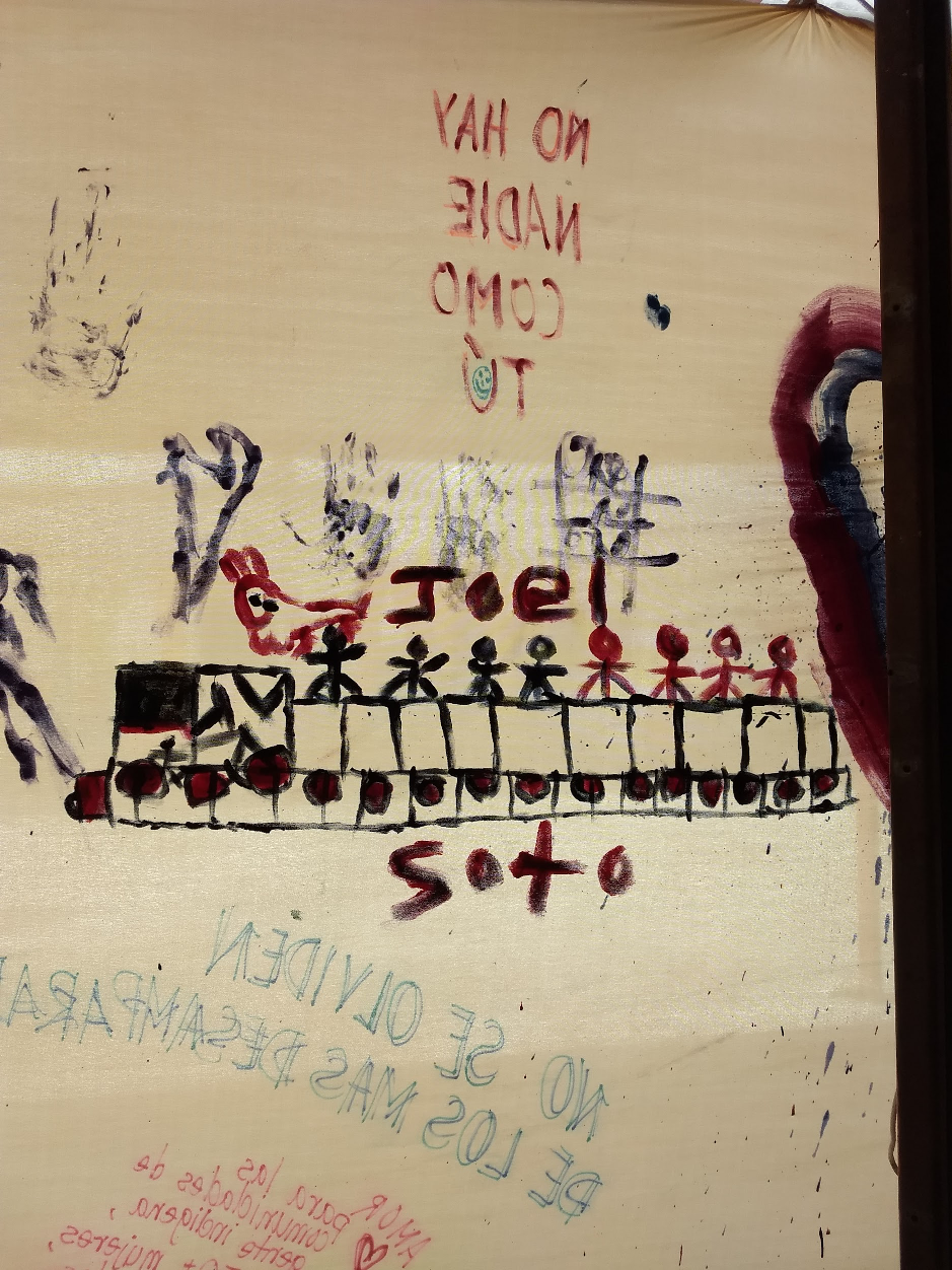 A piece of fabric with various images and messages painted on it, including an image of a train