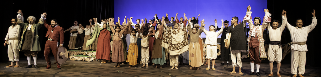 A row of actors raising their hands to take a bow