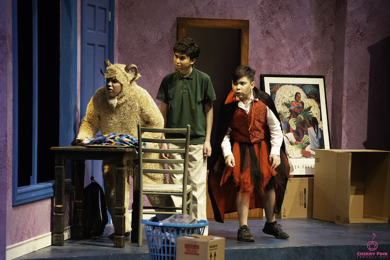 Three actors on stage in a performance of The Transition of Doodle Pequeño