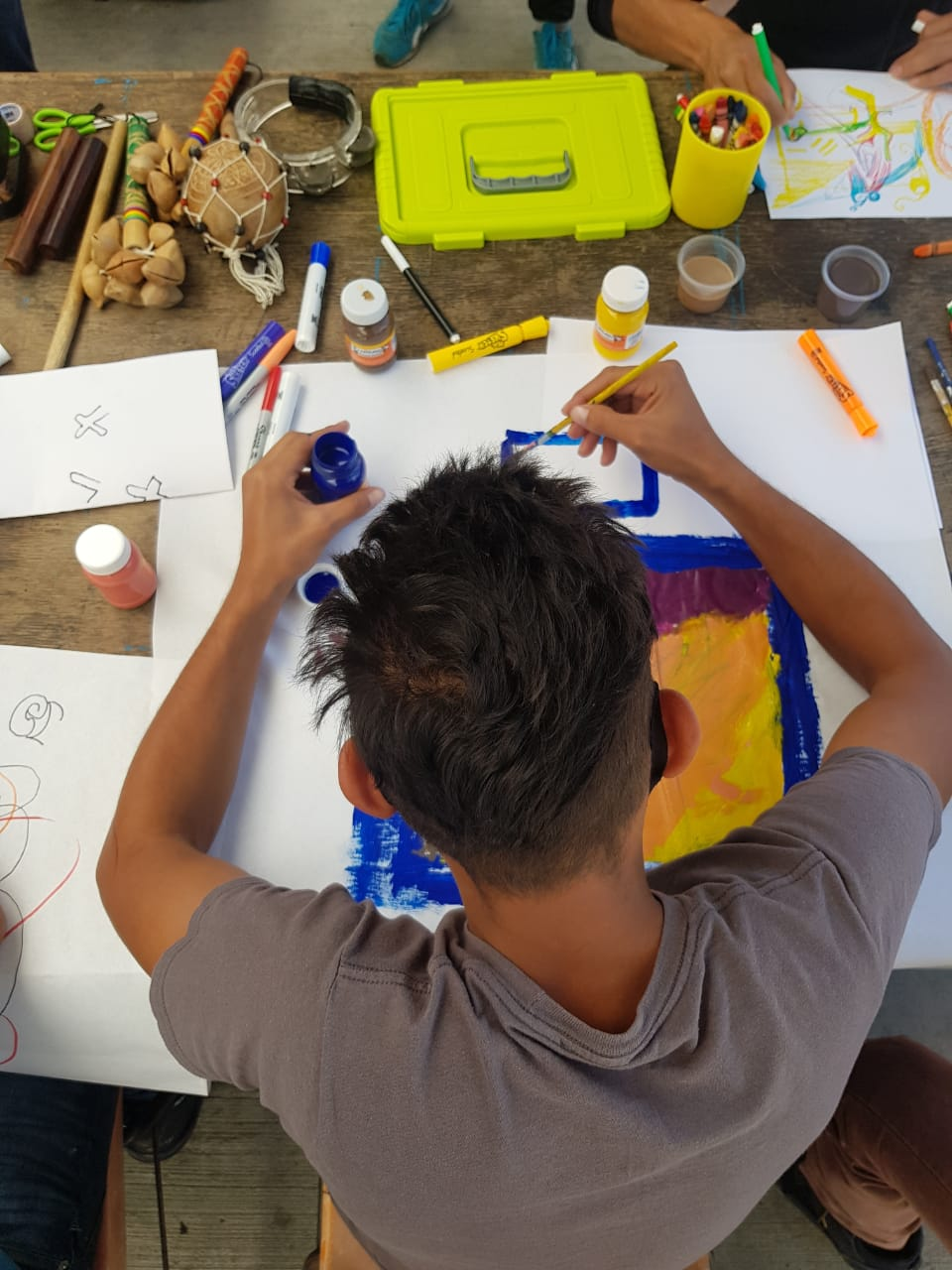 Overhead view of a person painting a colorful abstract image at a table full of art supplies