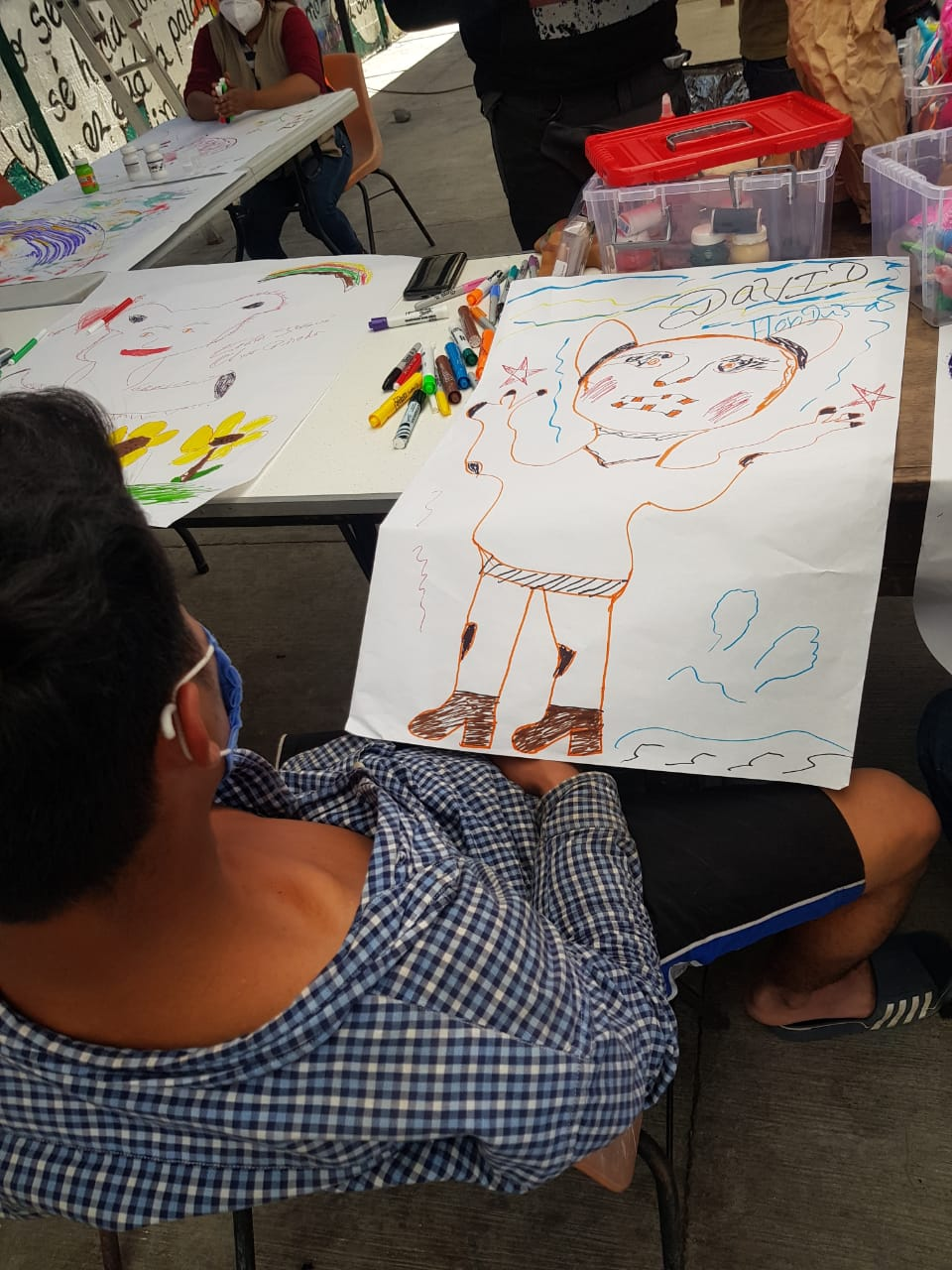 A man sits back in his chair looking at a picture he drew of a person at a table full of markers and other art supplies