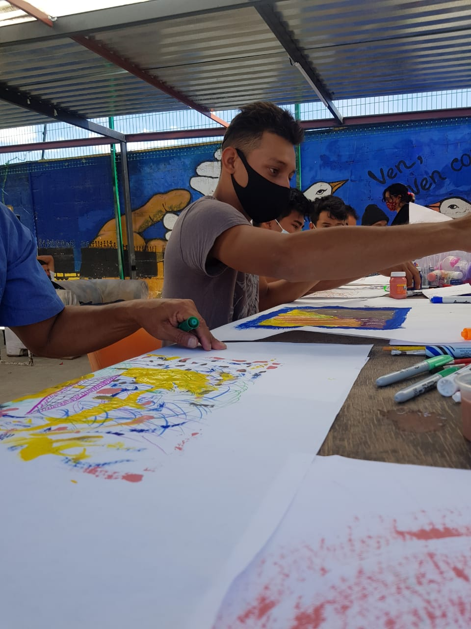 A row of workshop participants sit at a long table drawing and painting on large sheets of paper