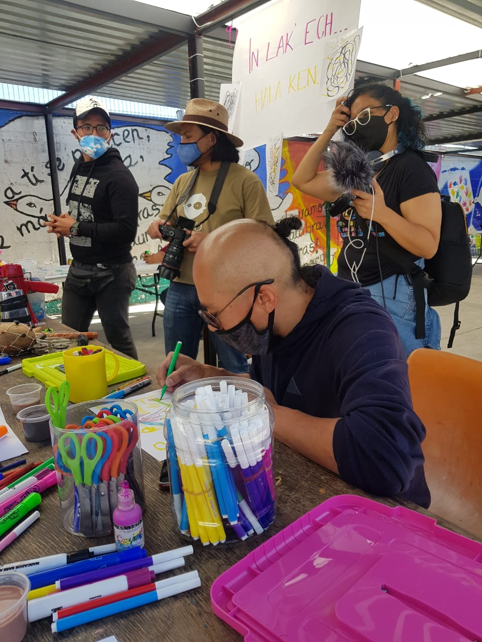 Salomón Santiago of La Quinta Teatro sits at a table full of art supplies, drawing, while three people stand behind him