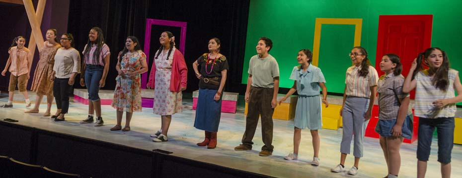 A line of youth actors stand across the front of the stage during a scene from The House on Mango Street