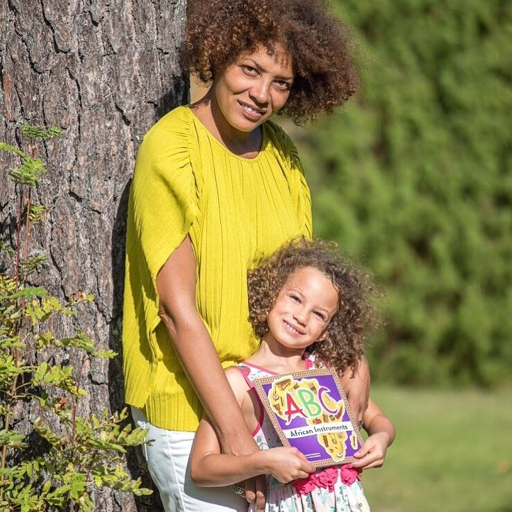 Woman with curly hair and bright yellow top and white trousers is smiling at the camera and holding a girl  is smiling at the camera and has her arms loosely at the sides of her 8 year old daughter who has similarly curly hair and is also smiling at the camera. The girl is holding a book called, \