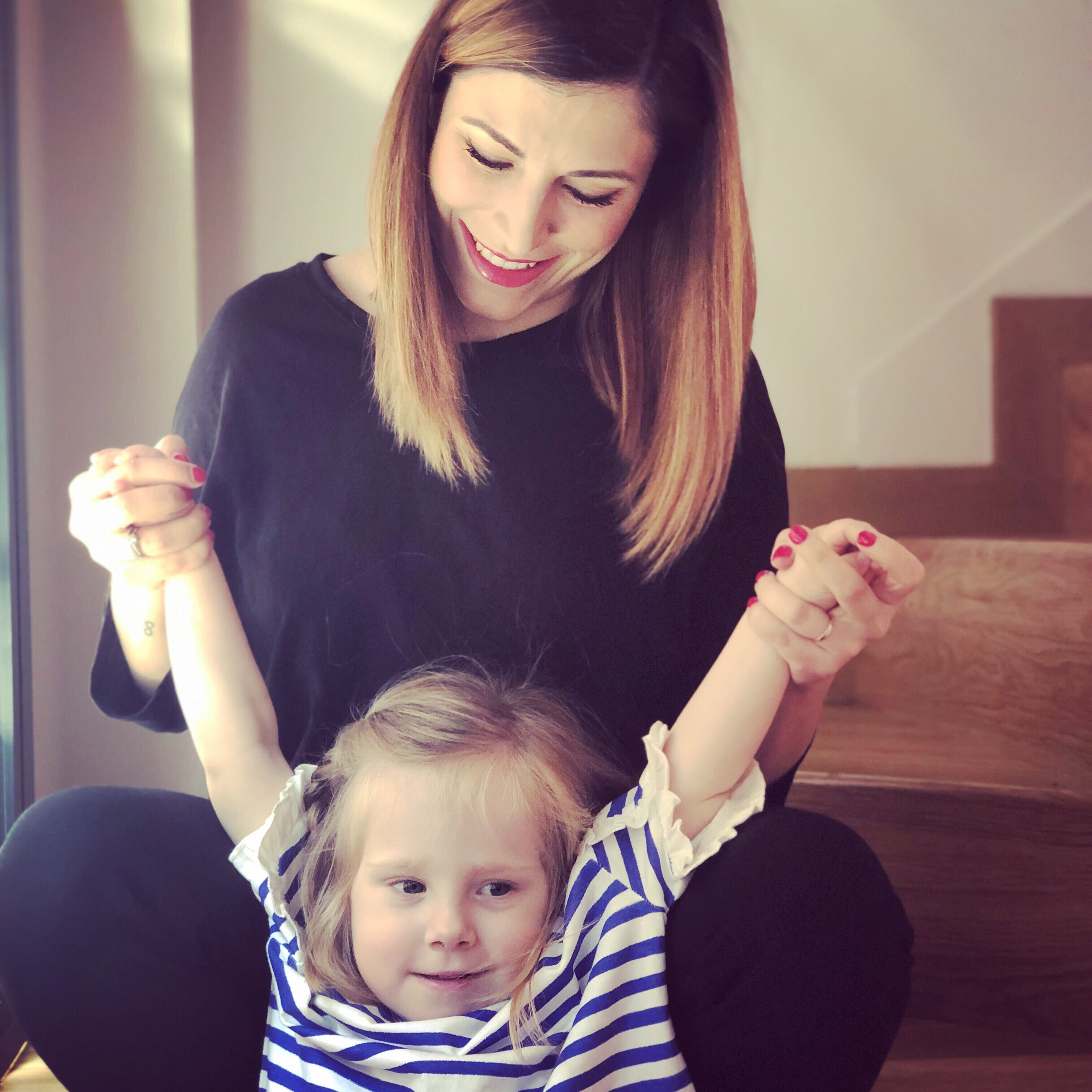 A woman with medium long light brown hair wearing all black  is smiling down at her 4 year old daughter and holding her arms up. The girl has is smiling and looking to the side. She is wearing a blue and white striped shirt.