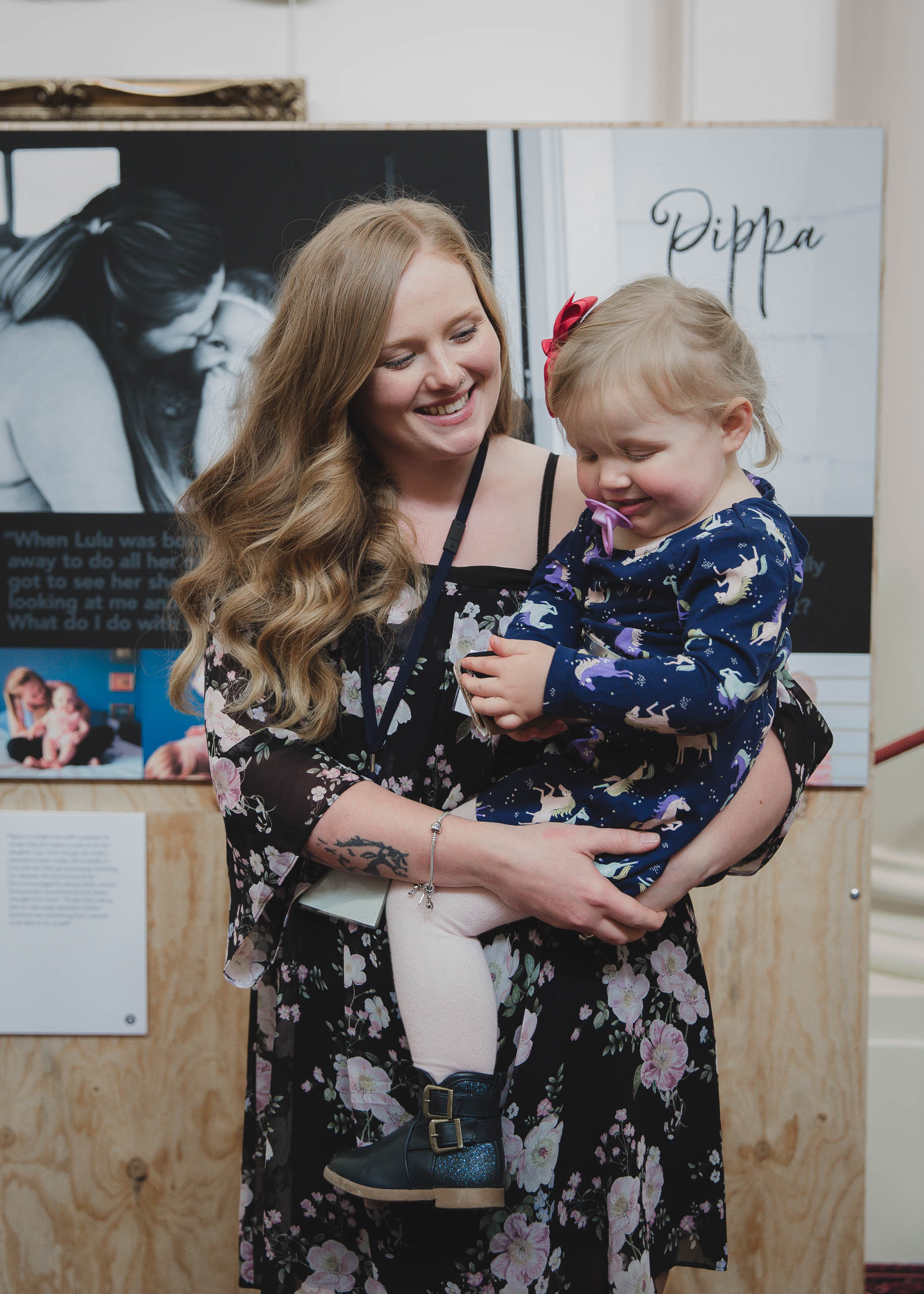 Rewriting_Motherhood_mum_Pippa_with_baby_Lulu_in_front_of_their_pictures_in_the_exhibition_2.jpg