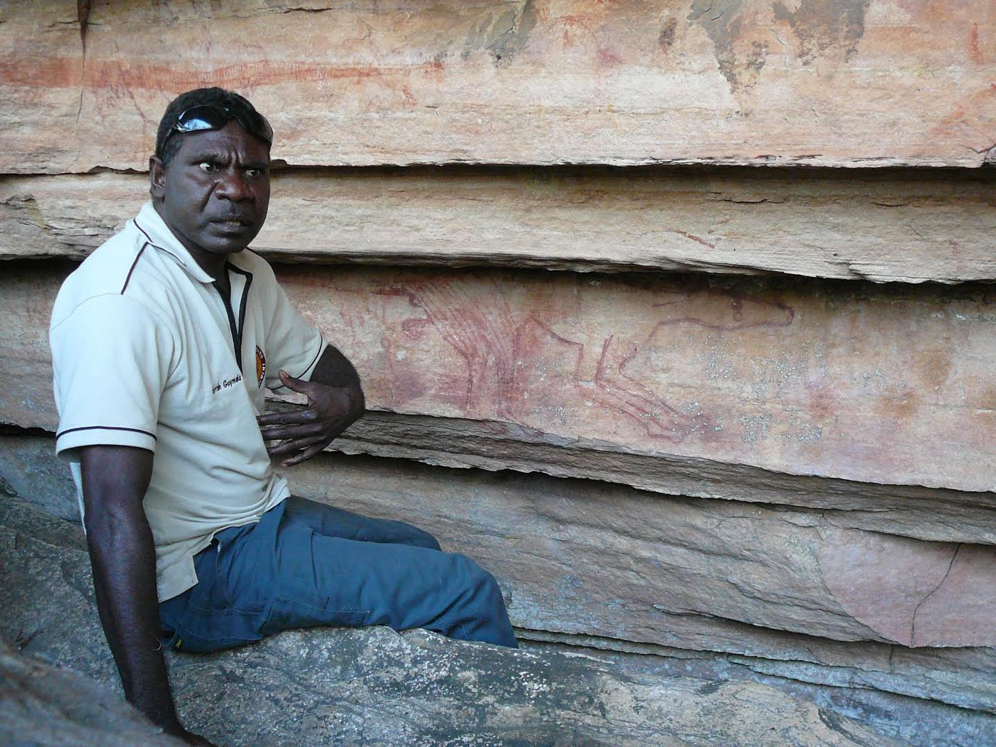 Terrah_Diliyoung_Guymala_Terrah_with_a_rock_art_depiction_of_a_thylacine_(Tasmanian_tiger)__which_is_widely_depicted_in_the_rock_art_of_the_Warddeken_IPA_Warddeken_Land_Management.jpg